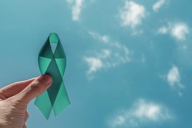 Hand met teal ribbon over blauwe hemel