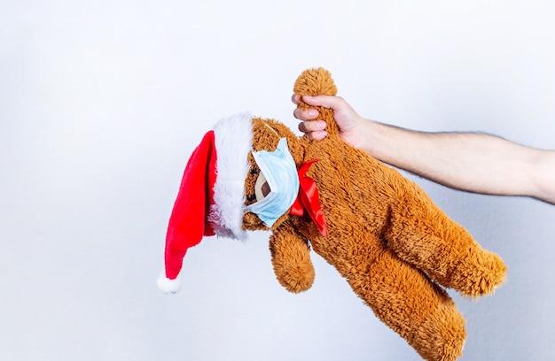Hand met teddybeer, met masker en kerstman glb, op wit
