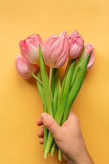 Hand met tedere roze tulpen onderaan pastel gele achtergrond. plat leggen. kopieer ruimte. plaats voor tekst. concept van internationale vrouwendag, moederdag, pasen. valentijnsdag liefdesdag.