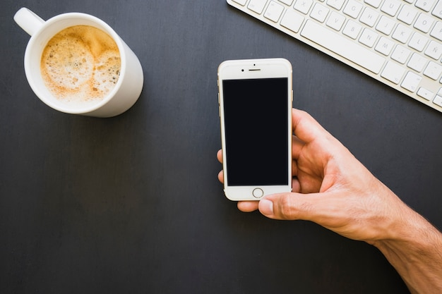 Hand met telefoon en koffie en toetsenbord op het bureau