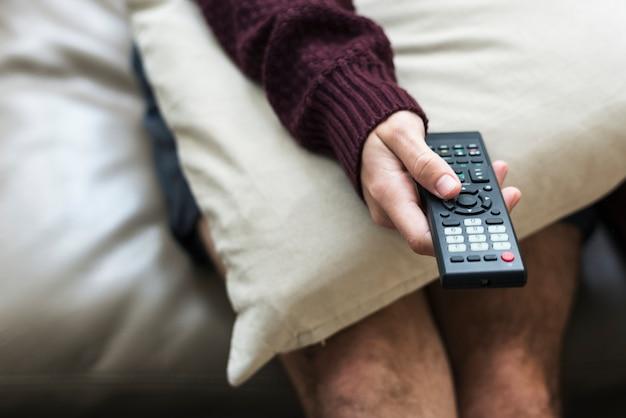 Hand met televisie afstandsbediening