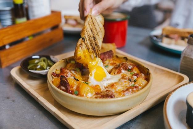 Hand met toast dompelen in cheesy ontbijt aardappelen met knapperige spek en gebakken ei.