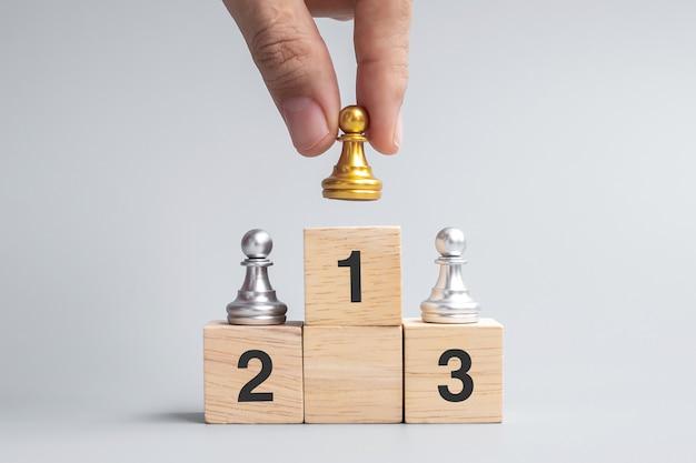 Hand met top van gouden schaakpion stukken of leider zakenman. overwinning, leiderschap, zakelijk succes, team, werving en teamwork concept
