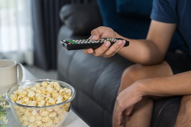 Hand met tv-afstandsbediening