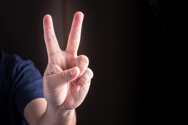 Hand met twee vingers omhoog. zucht van vrede of overwinning. ook het teken voor de letter v in gebarentaal.