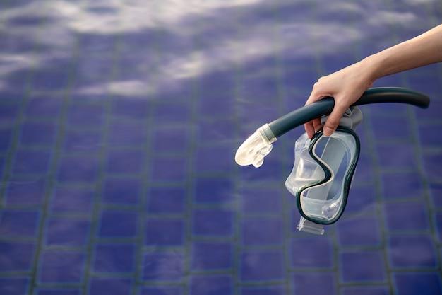 Hand met uitrusting voor snorkelmasker bij het zwembad.