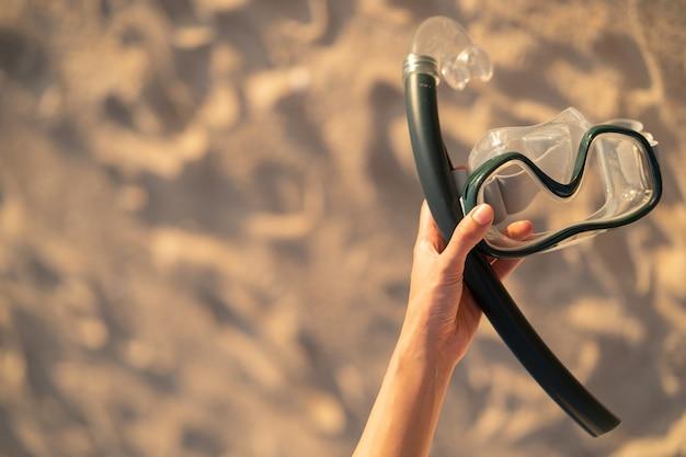 Hand met uitrusting voor snorkelmasker op het strand.