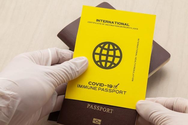 Hand met vaccinpaspoorten als bewijs dat de houder is ingeënt tegen covid-19, vereiste voor internationale reizen.