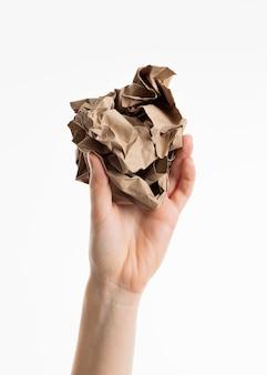Hand met verfrommeld papier