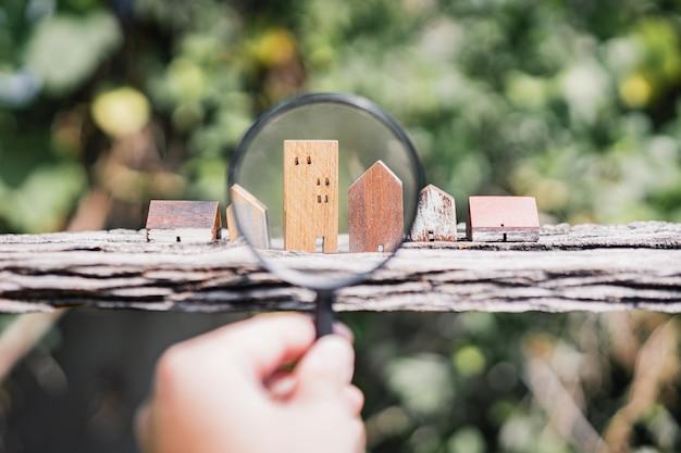 Hand met vergrootglas en kijken naar huis model,
