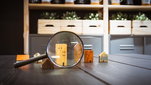 Hand met vergrootglas en kijken naar huismodel