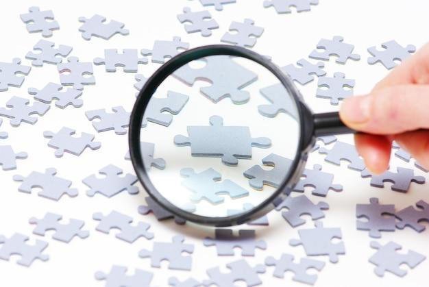 Hand met vergrootglas en puzzel op wit wordt geïsoleerd