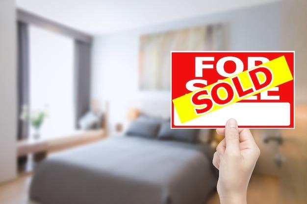 Hand met verkocht huis teken