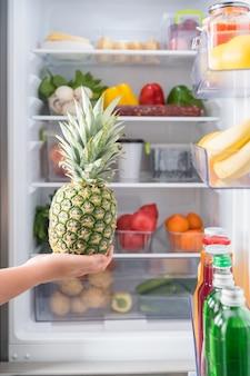 Hand met verse ananas tegen open koelkast