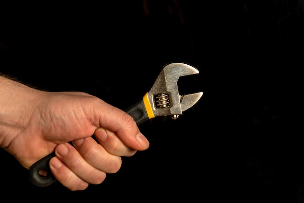 Hand met verstelbare moersleutel geïsoleerd