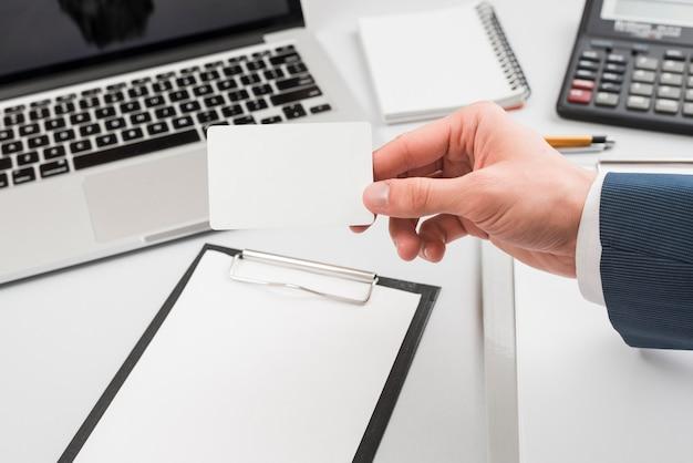 Hand met visitekaartje in kantooromgeving