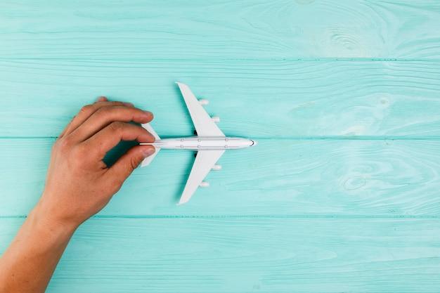 Hand met vliegtuigstuk speelgoed op turkoois