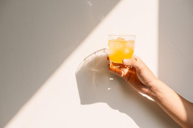 Hand met vol glas sinaasappelsap in de ochtend in de zomer