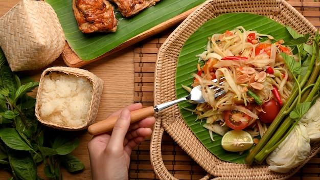 Hand met vork die somtum of papajasalade eet met plakkerige rijst en gegrilde kip in thaise stijl