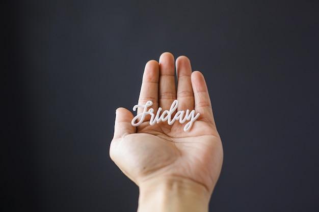 Hand met vrijdag woord op zwarte achtergrond