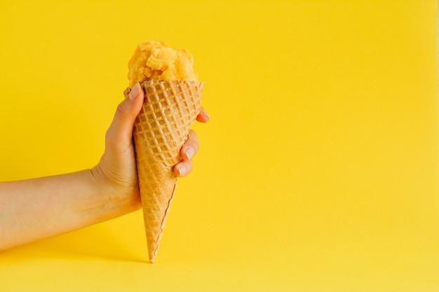 Hand met wafel kegel ijs geïsoleerd op een levendige gele, kopie ruimte