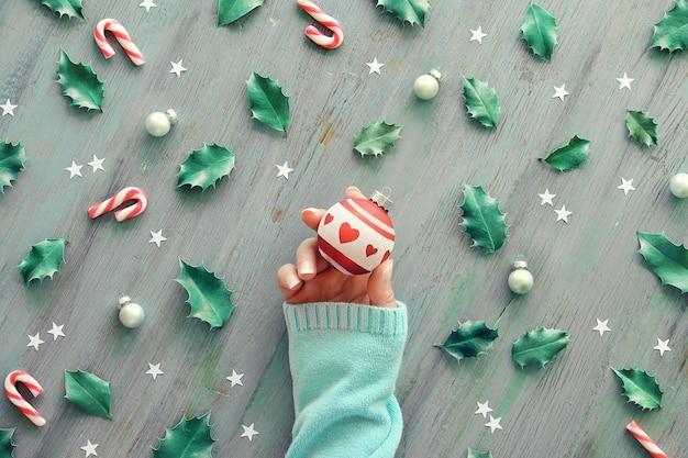Hand met wit en lees kerstbal.