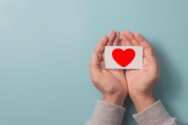 Hand met wit papier dat scherm rood hart blauwe achtergrond en kopie ruimte, liefde en valentijn dag concept afdrukt.