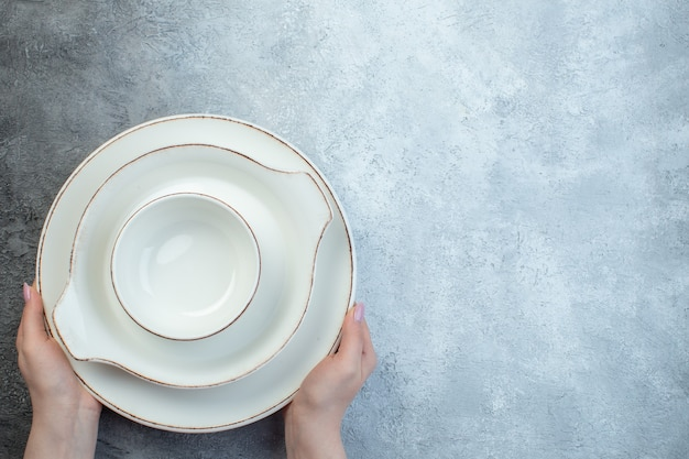 Hand met wit servies aan de rechterkant op half donker lichtgrijs oppervlak met verweerd oppervlak Premium Foto