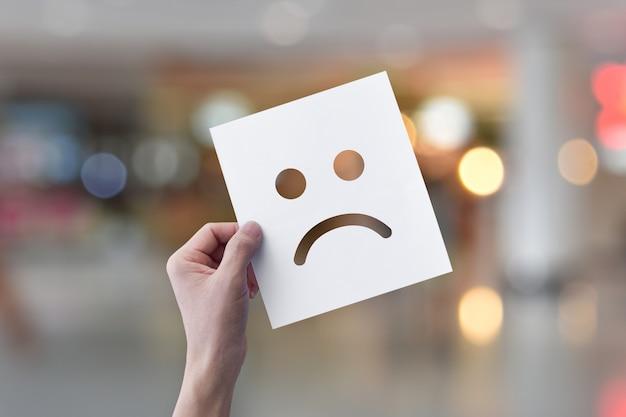 Hand met witboek met ongelukkig gezicht emoticons over lichte bokeh achtergrond.