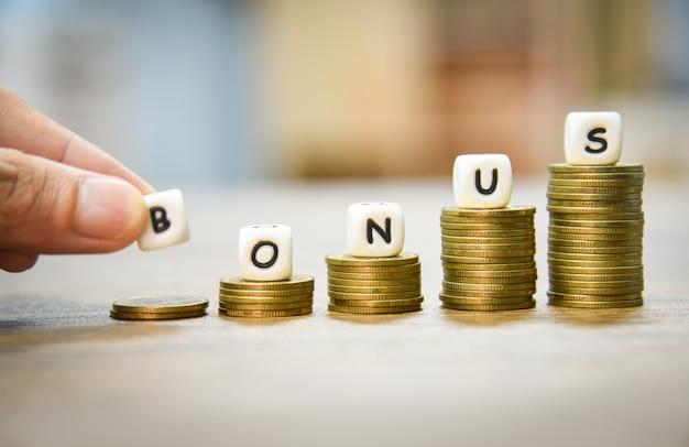 Hand met woorden van bonus op stapel munten trap