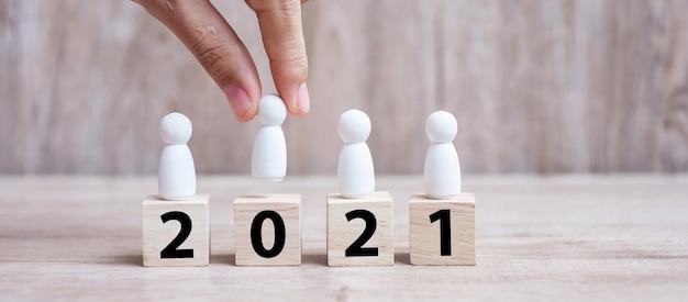 Hand met zakenman over blokbouw met 2021-tekst