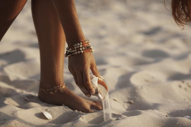Hand met zeeschelp op het strand in openlucht