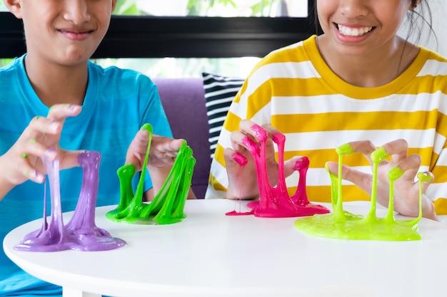 Hand met zelfgemaakte speelgoed genaamd slijm, broer en zus jongen en plezier en creatief zijn