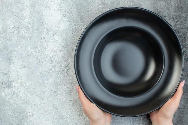Hand met zwart servies aan de linkerkant op een geïsoleerd grijs ijsoppervlak met vrije ruimte