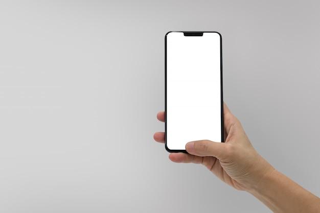 Hand met zwarte mobiele telefoon met leeg scherm geïsoleerd op grijs