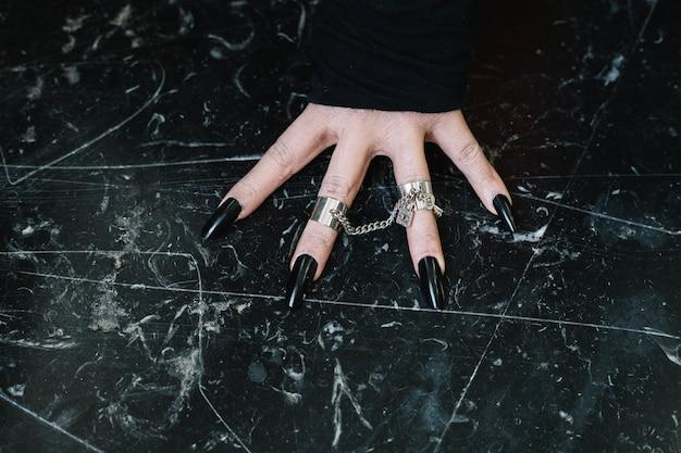 Hand met zwarte nagels
