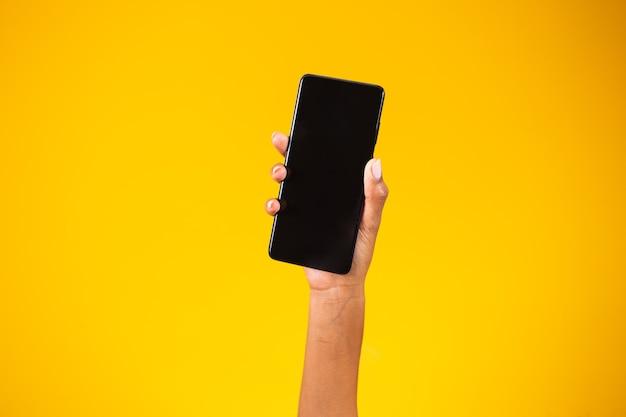 Hand met zwarte smartphone geïsoleerd op gele achtergrond