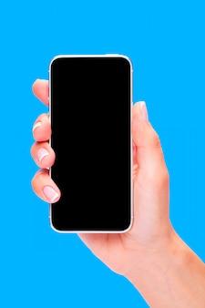 Hand met zwarte smartphone met leeg scherm op blauwe achtergrond