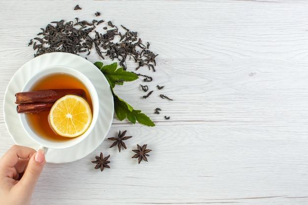Hand met zwarte thee in een witte kop rond droge thee en bladeren