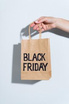 Hand met zwarte vrijdag papieren zak