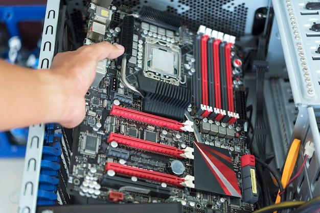 Hand moederbord met cpu in atx computerkast met kabel gestopt