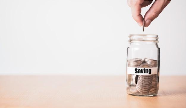 Hand munt aanbrengend geld pot om te besparen voor toekomstig concept.