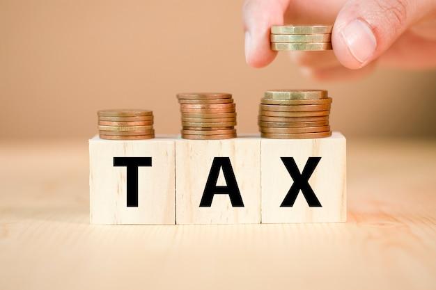 Hand munten op houten kubus en belasting formulering zetten. belastingconcept.