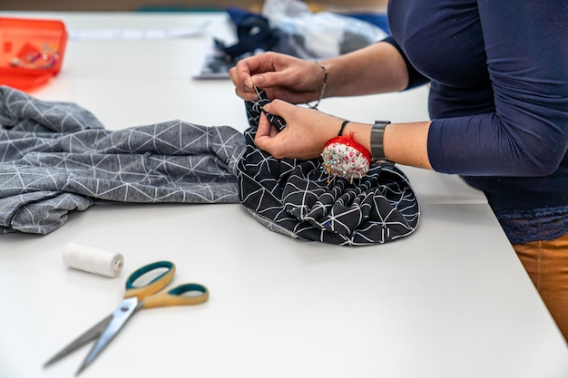 Hand naaien van kleding in kleermakerij.