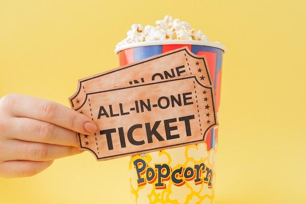 Hand neemt een bioscoopkaartjes en popcorn uit een papieren beker op een gele achtergrond. vrouw eet popcorn. cinema concept. plat liggen.