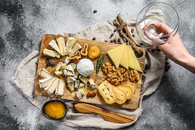 Hand neemt een stuk kaas van een kaasplateau geserveerd met noten en vijgen. grijze achtergrond. bovenaanzicht