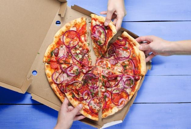 Hand neemt een stuk pizza op een blauwe tafel