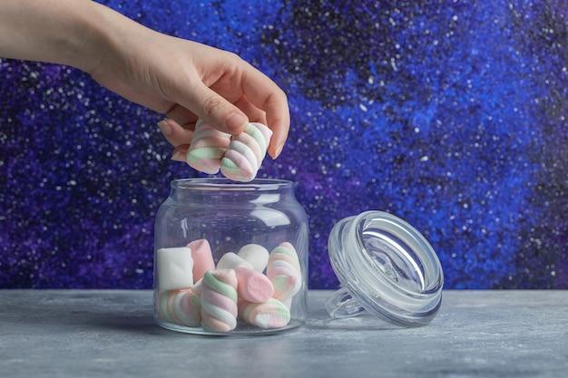 Hand nemen marshmallows uit glazen pot op een kleurrijke muur.