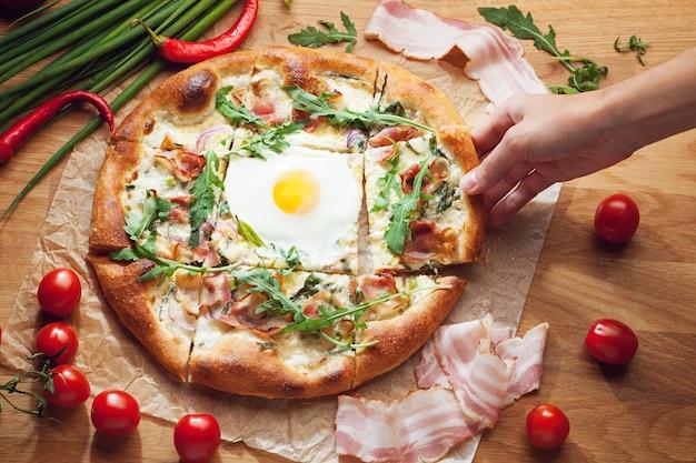 Hand nemen plak van heerlijke pizza geserveerd op houten tafel
