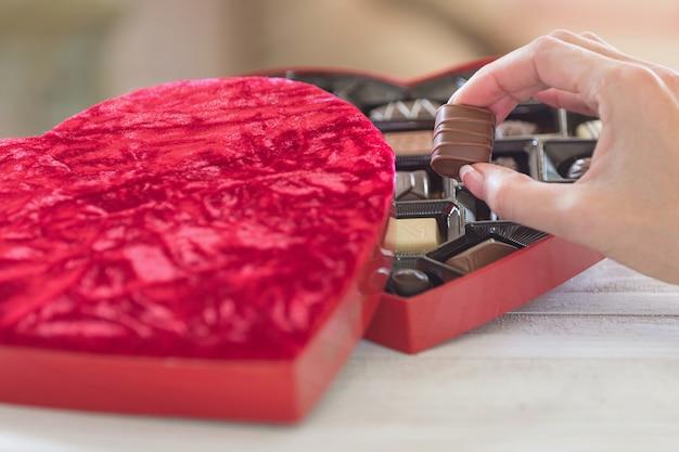 Hand nemen van een truffel van een hartvormige doos chocolaatjes
